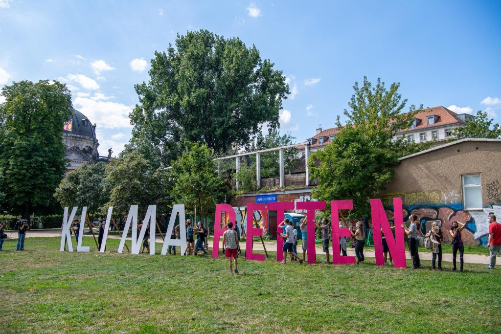 """Eine Wiese mit großen Holzbuchstaben """"Klima retten"""", drumherum stehen Personen, im Hintergrund Bäume und Häuser."""